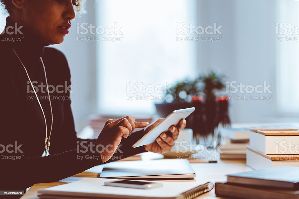 Elegance young woman using digital tablet in an office Elegance young woman using a digital tablet in an office, focus on hands. Adult Stock Photo