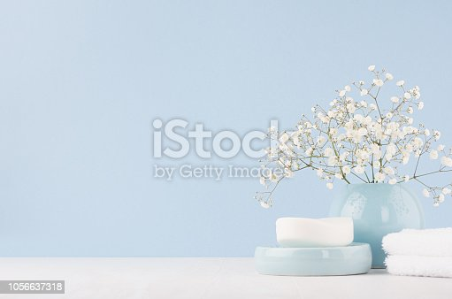 istock Elegant acessories for dressing table - soft pastel blue ceramic bowls, white flowers, products for skin and body care on white wood board and blue wall. 1056637318