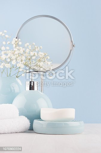 1056636898istockphoto Elegant acessories for dressing table - soft pastel blue ceramic bowls, white flowers, circle mirror, products for skin and body care on white wood board and blue wall. 1070932224