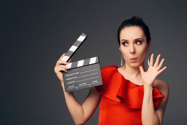 elegante schauspielerin im roten kleid holding kino schindeln - film oder fernsehvorführung stock-fotos und bilder