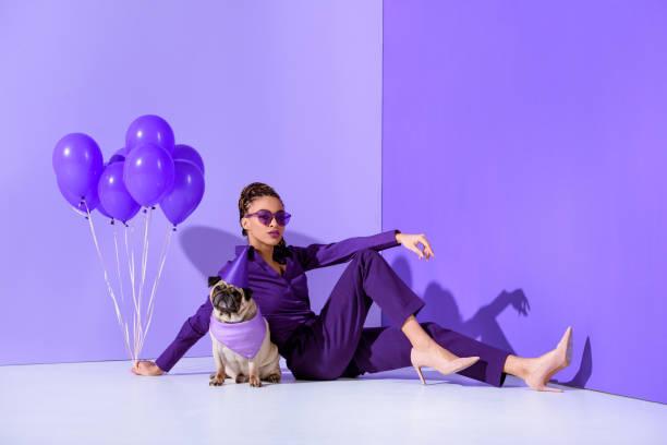 elegant african american girl posing with purple balloons and pug, ultra violet trend - mulher balões imagens e fotografias de stock