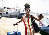 Front view of elegant african woman taking selfie at habor