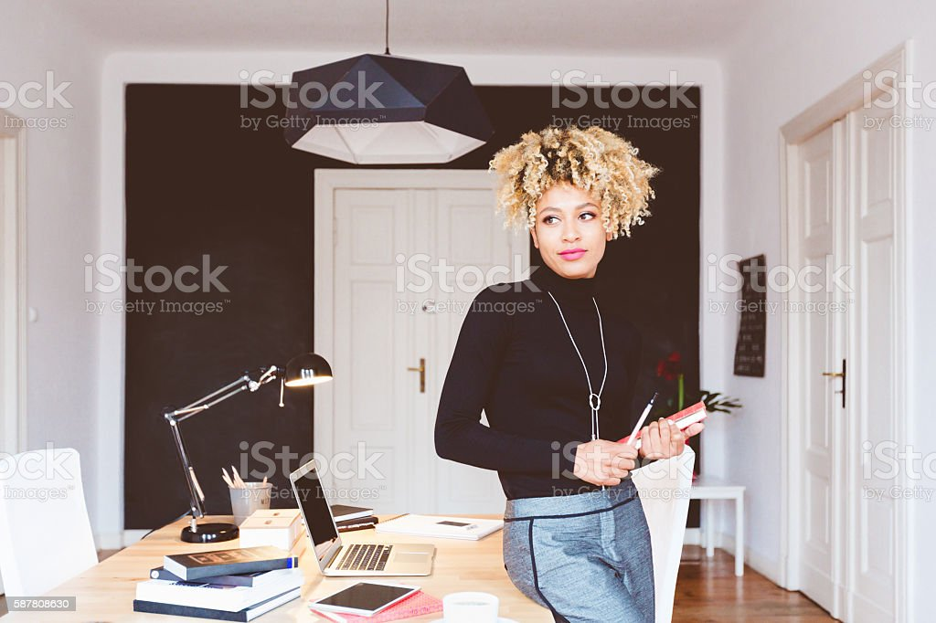 Elegant afro american young woman in a home office Beautiful afro american young woman in a home office, standing at the desk. Adult Stock Photo