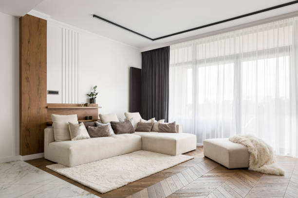 Elegant and comfortable living room Elegant and comfortable designed living room with big corner sofa, wooden floor and big windows curtain stock pictures, royalty-free photos & images