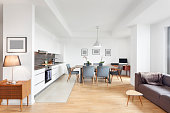 Modern loft apartment with open kitchen, dinning table and couch. The floor is hardwood and the whole image is very elegant and modern.