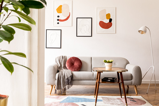Elegant and vintage apartment interior with classic wooden furniture, grey sofa, retro coffee table, lamp and mock up posters gallery. Brwon parquet, stylish carpet and plants. Bright space.