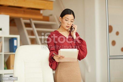 836871418 istock photo Elegant Asian Businesswoman Speaking by Phone 1208772501