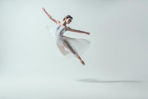 elegant ballet dancer in white dress jumping in studio