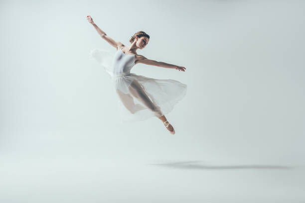elegant ballet dancer in white dress jumping in studio stock photo