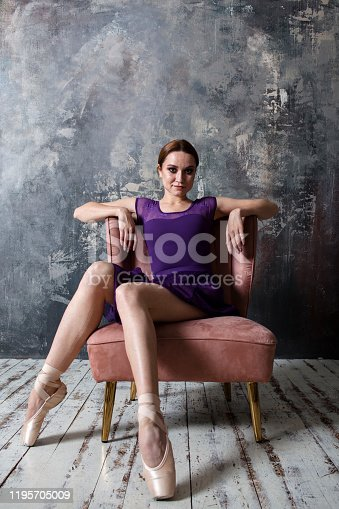 elegant ballet dancer is sitting in the studio on the armchair