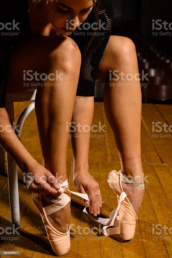 elegant ballet dancer tying her pointe shoes stock photo