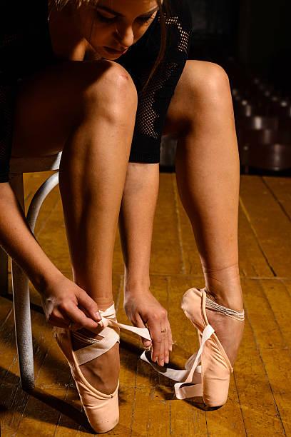 elegant ballet dancer tying her pointe shoes stock photo