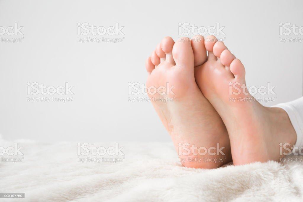 Elegant bare feet. Beautiful groomed woman\'s feet on the fluffy...
