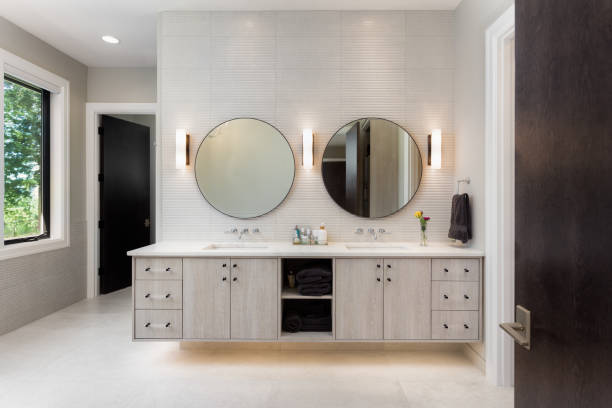 Elegant Bathroom in New Luxury Home with Two Sinks and Circular Mirrors stock photo