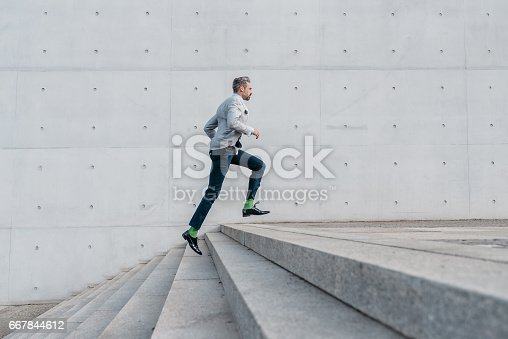 istock elegant bearded businessman running up stairs outdoors 667844612