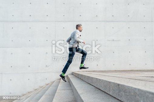 istock elegant bearded businessman running up stairs outdoors 909444910