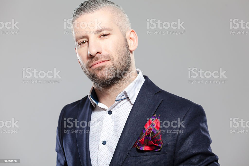 Elegant bearded grey hair businessman in fashioable outfit Portrait of elegant bearded grey hair businessman in fashionable outfit. Standing against grey background and looking at camera. Studio shot, one person.  2015 Stock Photo