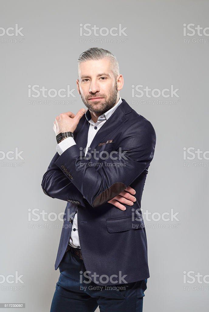 Elegant bearded grey hair businessman, Studio Portrait Portrait of elegant bearded grey hair businessman wearing suit, looking at camera. Studio shot, one person, grey background. Adult Stock Photo
