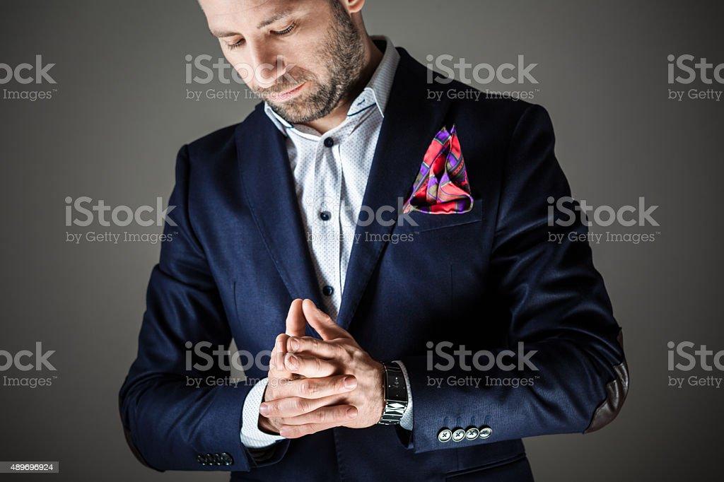 Elegant bearded man wearing jacket Portrait of elegant bearded businessman wearing jacket. Standing against dark grey background. Studio shot, one person.  2015 Stock Photo