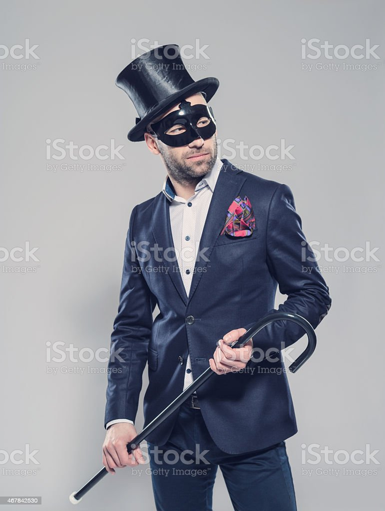 Elegant bearded man wearing top hat and carnival mask Portrait of elegant bearded businessman wearing jacket, top hat and carnival mask. Standing against grey background, holding walking stick in hands. Studio shot, one person.  2015 Stock Photo