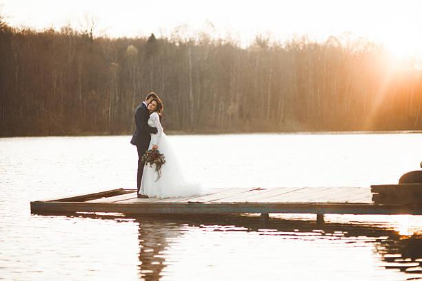 Elegant beautiful wedding couple posing near a lake at sunset stock photo