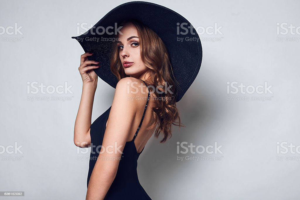 Elegant beautiful woman in a black dress and hat - foto de stock