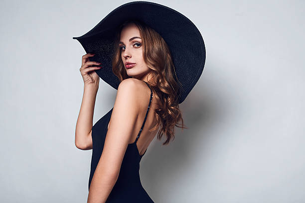 Elegant beautiful woman in a black dress and hat stock photo