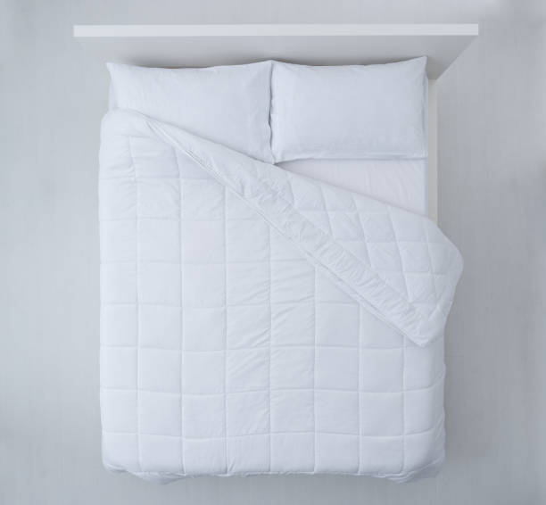 Elegant bed top view Elegant bed with soft white duvet, bedding and pillows, top view duvet stock pictures, royalty-free photos & images