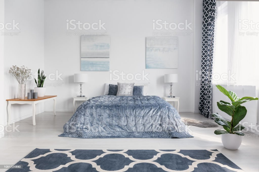 Elegant bedroom interior with big comfortable bed with blue bedding,...