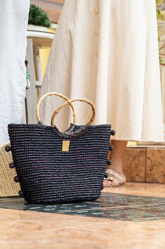 elegant black purse, woven, handmade accessory on the floor, fashionable object in studio