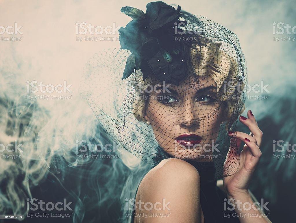 Elegant blond retro woman  wearing little hat with veil stock photo