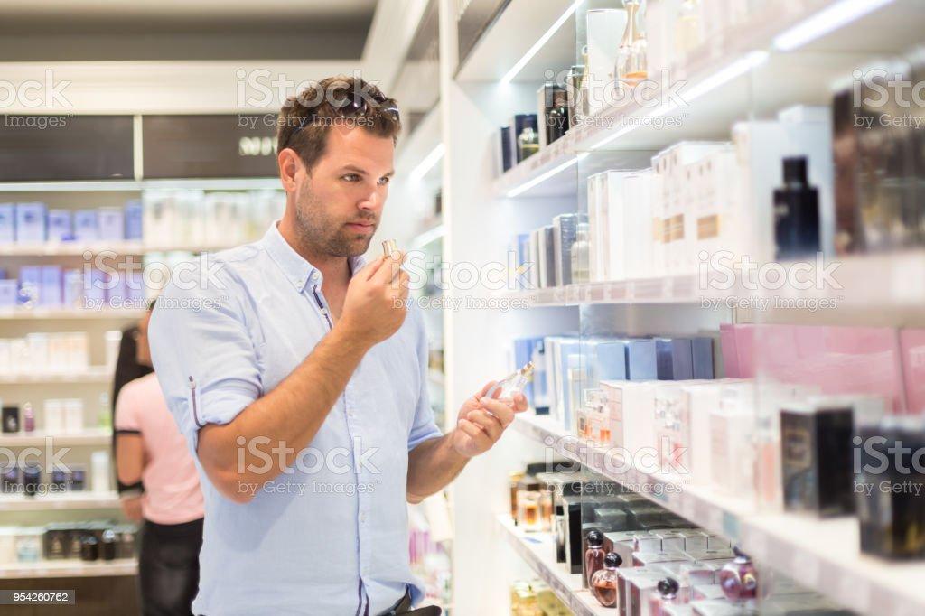 Elegante blonde junge Frau Parfüm im Ladengeschäft zu wählen. – Foto