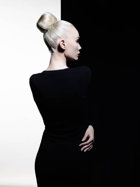 elegante blondine in geometrischen schwarzen und weißen hintergrund - vogue muster stock-fotos und bilder