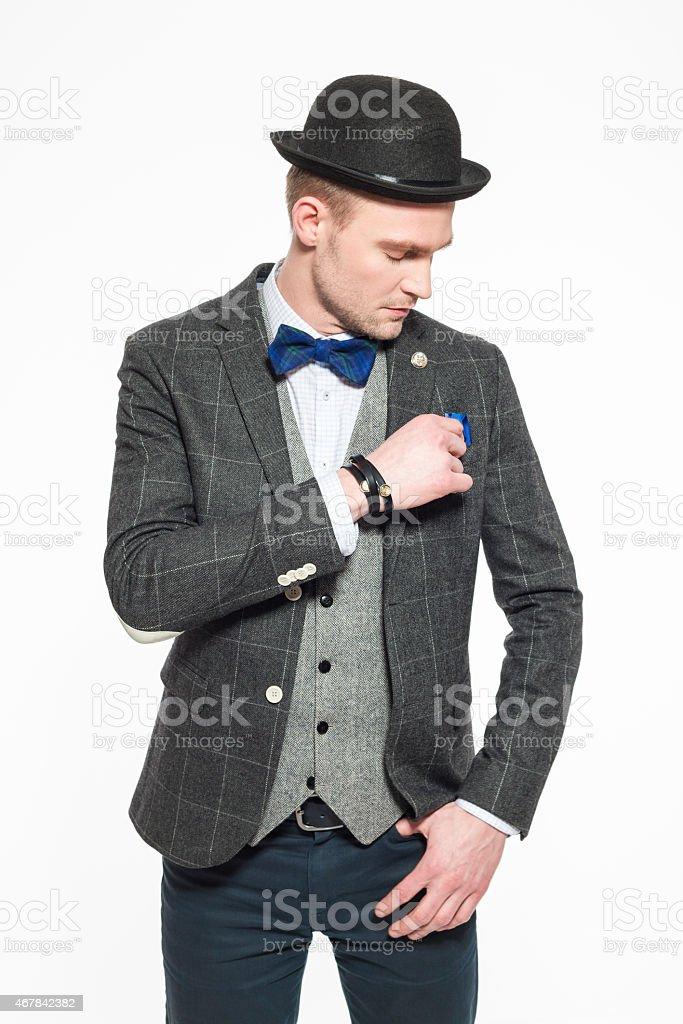 Elegant blonde man wearing tweed jacket, bow tie and bowler stock photo