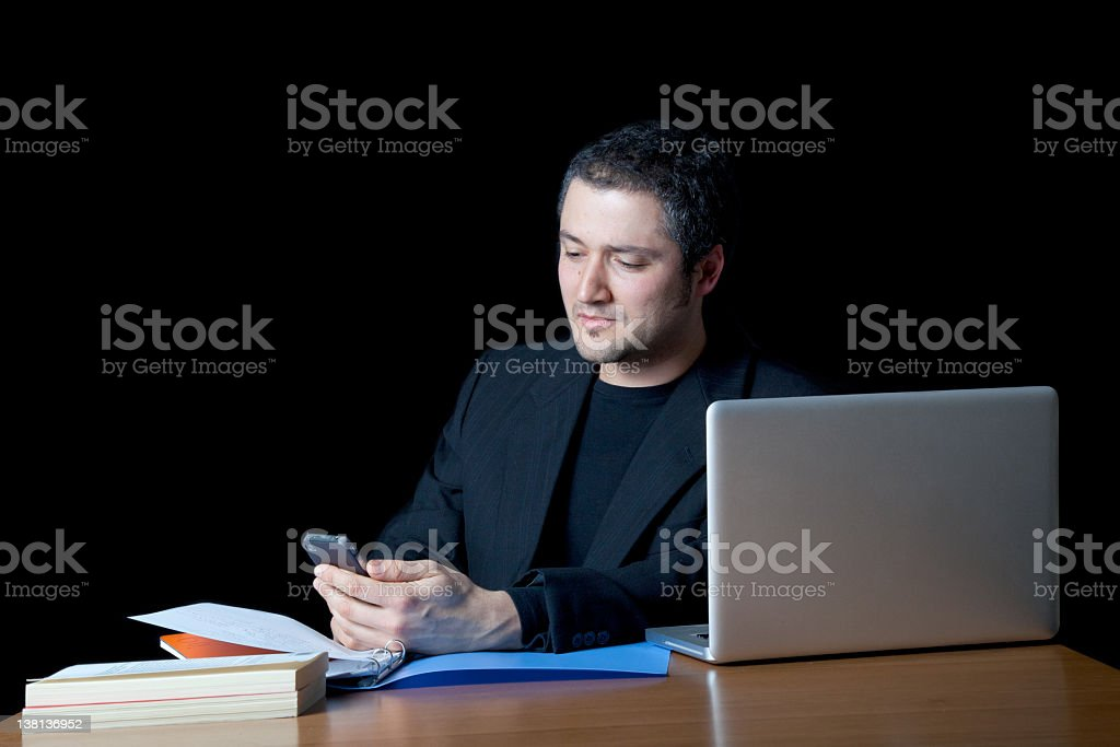 Elegant boy with laptop is consulting his mobile phone stock photo