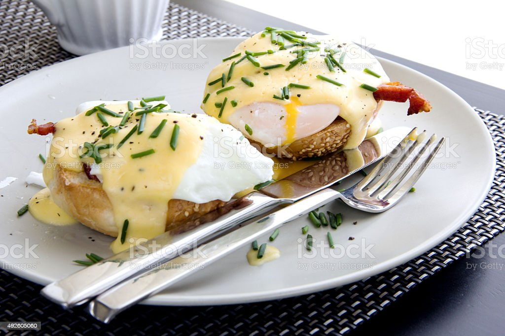 Elegant breakfast consists of eggs Benedict and delicious hollandaise sauce stock photo