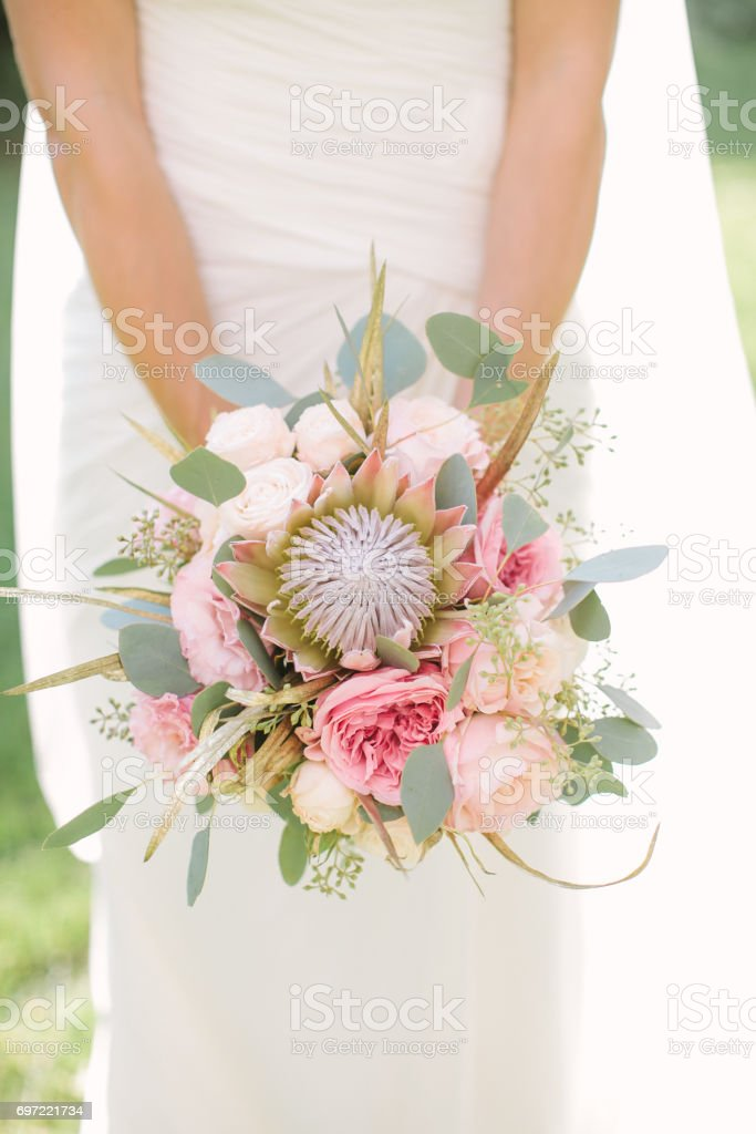 elegant bride in a white dress and veil holding in hand a wedding bouquet from gently pink roses, peonies and eucalyptus stock photo