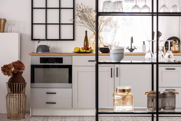 Elegantes helles Kücheninnere mit weißen Schränken und schwarzem Regal – Foto