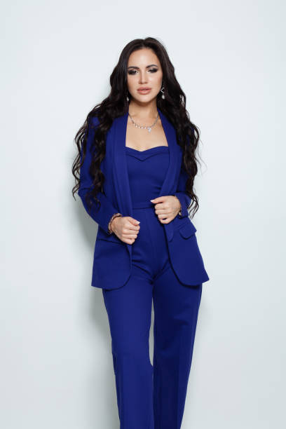 elegante brünette-model im jumpsuit vor weißem hintergrund - jumpsuit blau stock-fotos und bilder