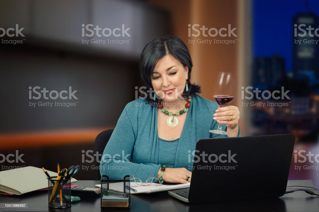 Middle aged brunette biz lady in light blue merino suit chatting