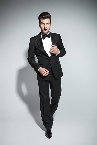 elegant business man fixing his collar - tuxedo stock photos and pictures