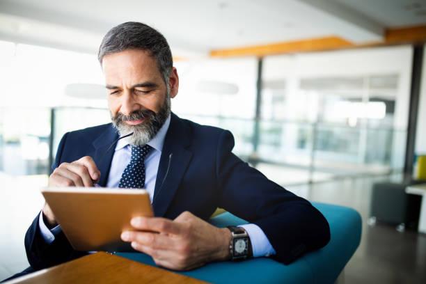 Elegant business multitasking multimedia man using devices stock photo