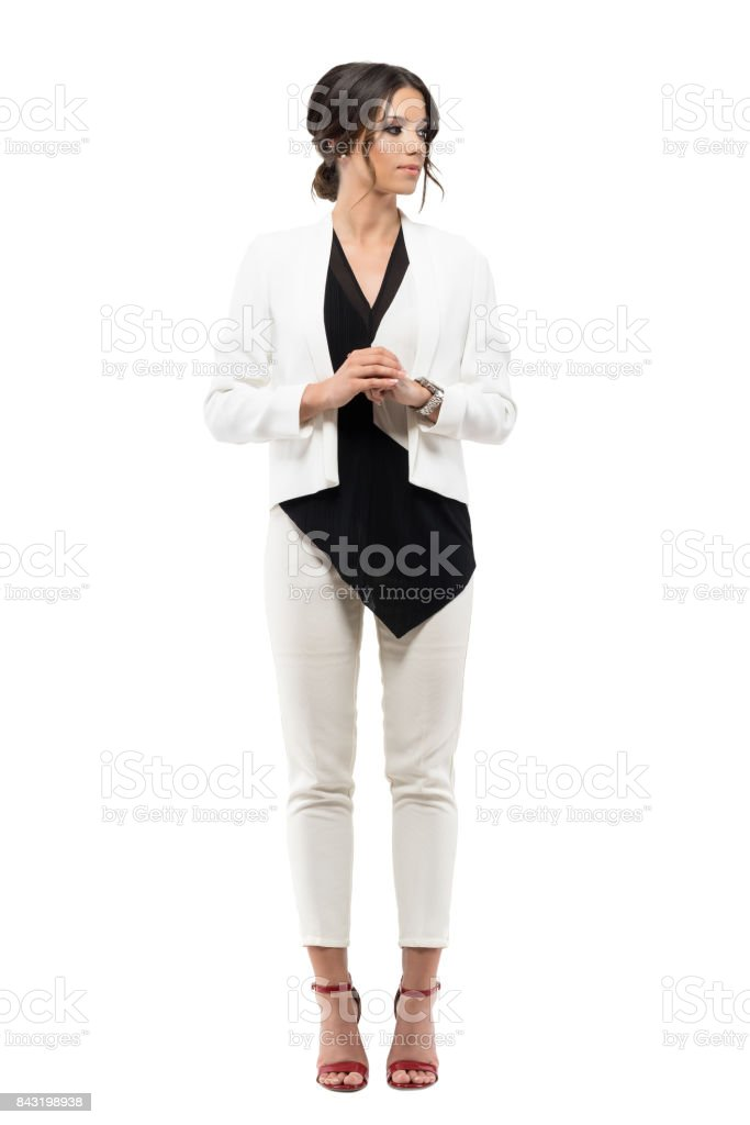 Elegant business woman in suit standing in formal posture with hands clasped looking away. stock photo
