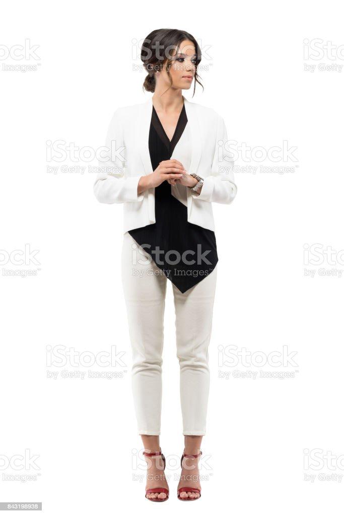 Mujer de negocios elegante en traje de pie en postura formal con las manos cruzadas mirando lejos. - foto de stock