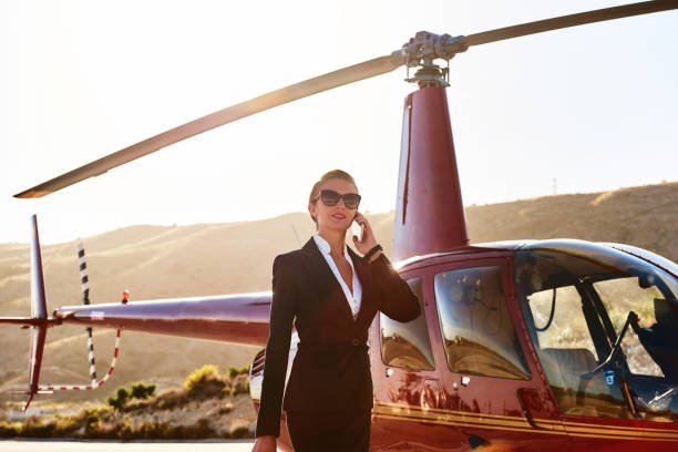 Elegant business woman Elegant business woman talking by phone near the helicopter. Business, success and luxury concept millionnaire stock pictures, royalty-free photos & images
