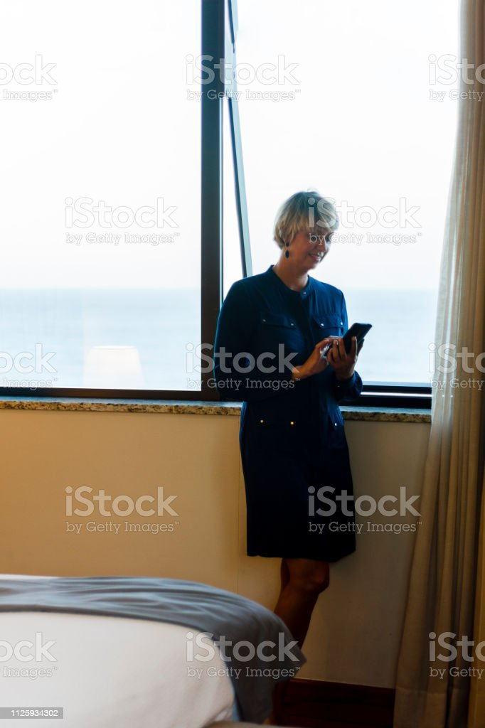 Elegant business woman using smartphone by the window of a hotel room.