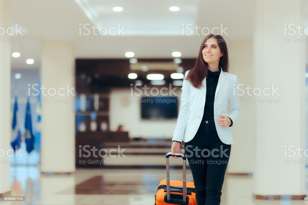 Elegant Business Woman with Travel Trolley Luggage in Hotel Lobby stock photo