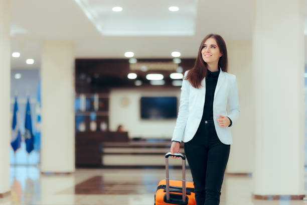 elegant business woman with travel trolley luggage in hotel lobby - guest stock pictures, royalty-free photos & images