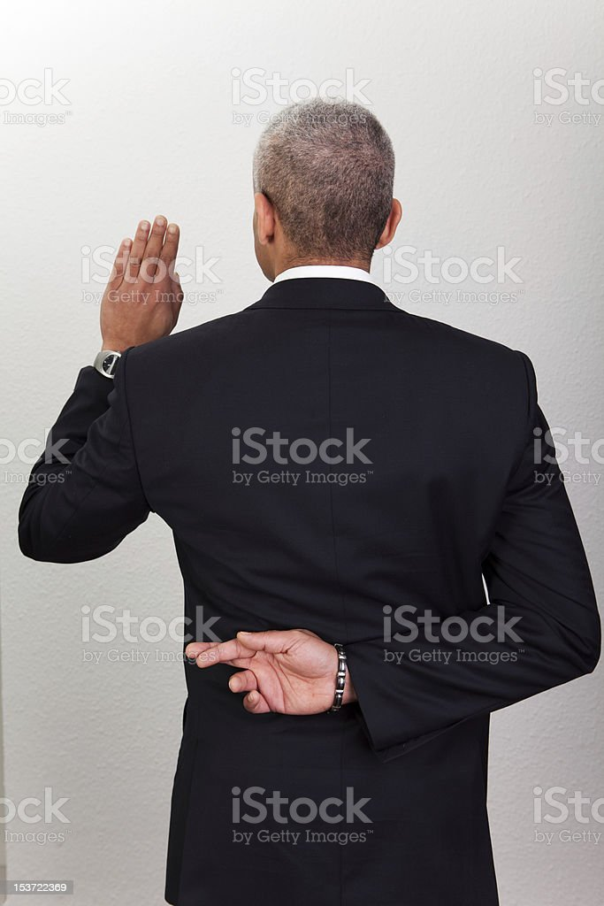 Elegant businessman crossing his fingers behind his back royalty-free stock photo
