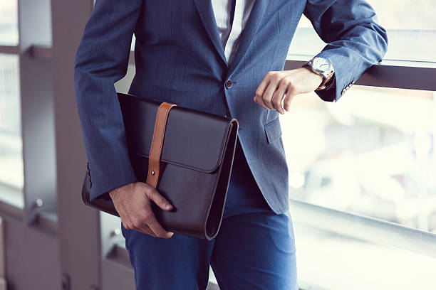 Elegant businessman in the office Businessman wearing suit posing in an office, holding leather briefcase and checking the time. briefcase stock pictures, royalty-free photos & images